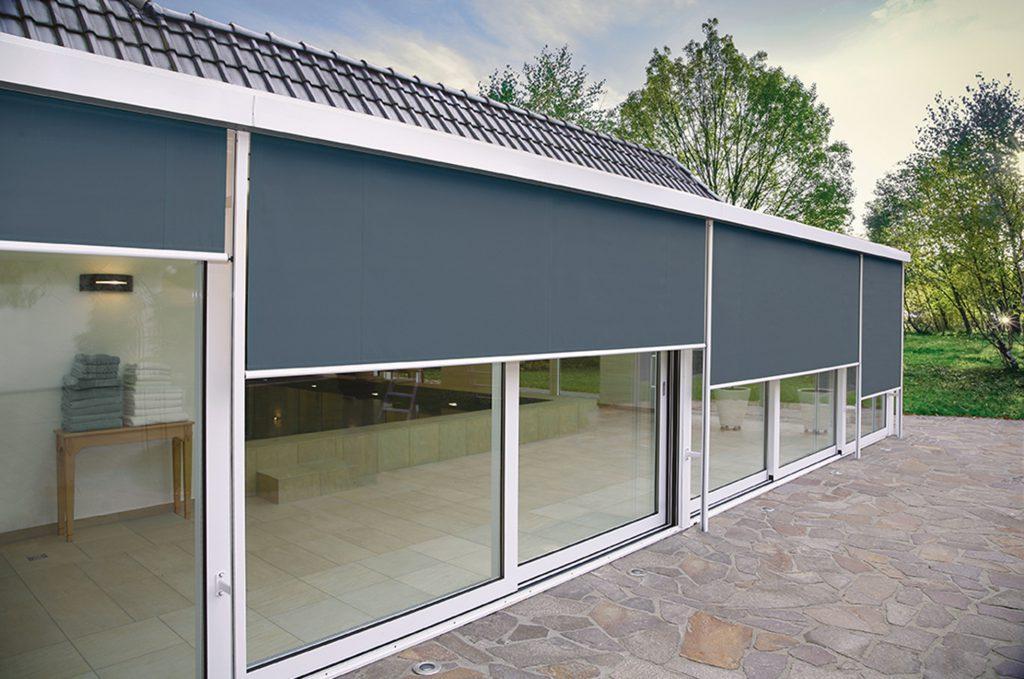 erwilo Senkrechtmarkise als Sichtschutz und Sonnenschutz mit motorisiertem grauem Tuch direkt am Fenster montiert.