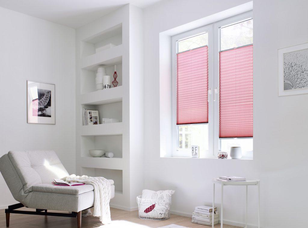 Einzigartiges KADECO Plissee als Highlight in roter Farbe im schlichten Wohnzimmer.